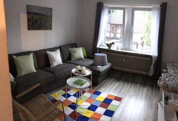 3Sitzer-Couch mit Recamiere, bunter Teppich, zwei Tablett-Tischchen, Laminatboden, graue Gardinen