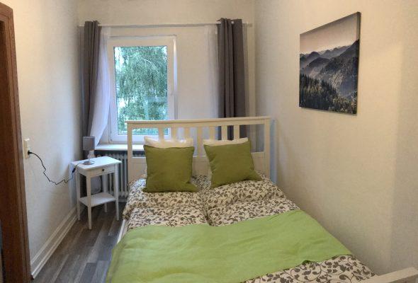 weißes Bett, 1,40m Breite, graue Bettwäsche, Zierkissen in grün und weiß, grüner Bettläufer, graue Gardinen, Laminatboden